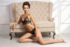 Woman in black lingerie set sitting on floor and leaning on sofa